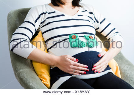 Pregnant woman sitting with baby's socks on belly - Stock Photo