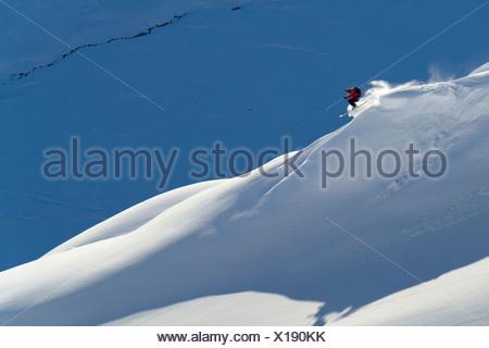Man backcountry skiing powder snow on the south face of Eddies Ridge, Turnagain Pass, Kenai Mountains in Southcentral Alaska - Stock Photo