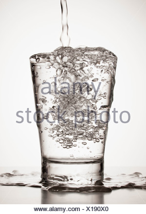 Water overflowing from glass - Stock Photo