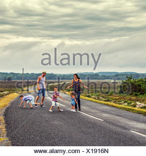 Family dancing on road - Stock Photo