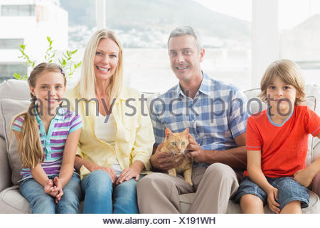 Portrait of happy family sitting with cat on sofa - Stock Photo