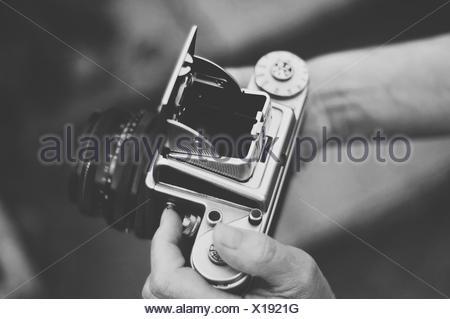 United Kingdom, England, Warwickshire, Stratford-upon-Avon, Woman holding old vintage medium format camera - Stock Photo