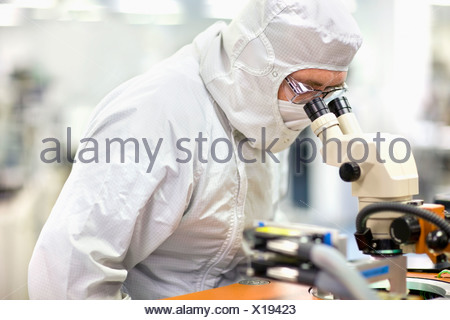 Scientist in clean suit examining silicon wafer in telescope in laboratory - Stock Photo