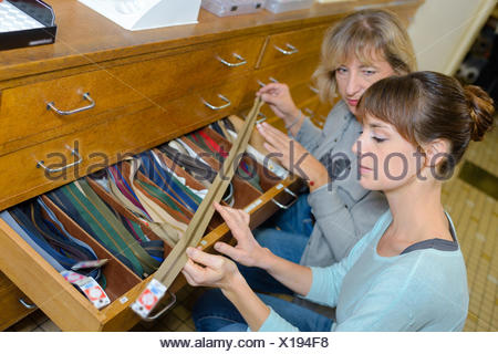Woman choosing zip from drawer in store - Stock Photo