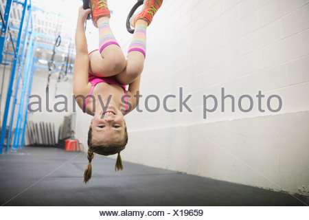Girl hanging upside down from gymnastic rings - Stock Photo