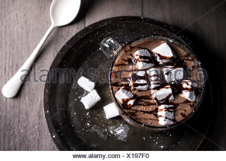 Overhead view of hot cocoa in large glass mug with marshmallows and chocolate drizzle. - Stock Photo