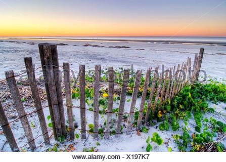 A beach fence at sunset on Hilton Head Island, South Carolina. - Stock Photo