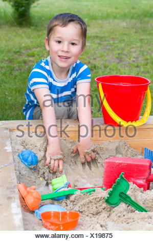 little boy plays in a sandbox - Stock Photo