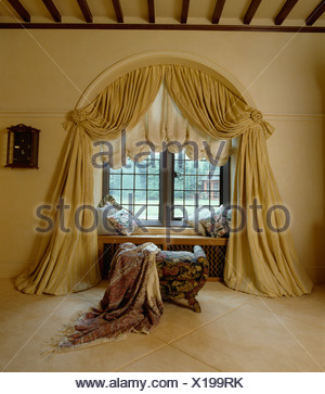 Cream Draped Curtains And Festoon Blind On Arched Window In Bedroom With  Patterned Throw Onstool In