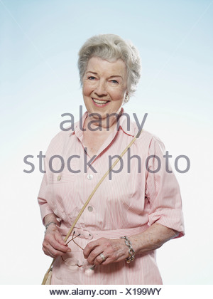 Profile of smiling senior woman holding her glasses - Stock Photo