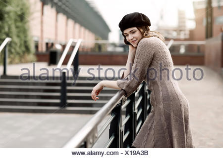 Portrait of young woman wearing beret and knitted dress leaning on a railing - Stock Photo