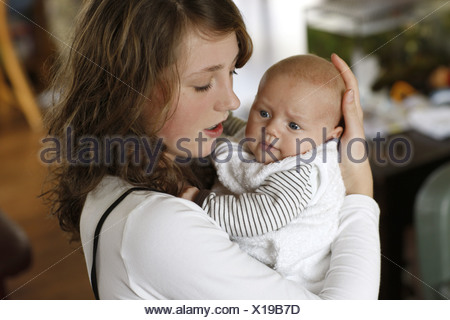 Underage teenage mum loves her baby, she is holding the baby tender in her arms. - Stock Photo