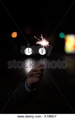 Close-Up Of Hand Holding Sparklers At Night - Stock Photo
