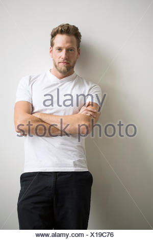 Portrait of confident blonde man with arms crossed - Stock Photo