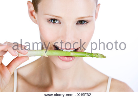 A young woman holding a piece of asparagus in her mouth - Stock Photo