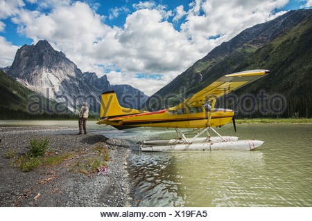 Man Stands On The Shores Of Glacier Lake By Float Plane; Northwest Territories, Canada - Stock Photo