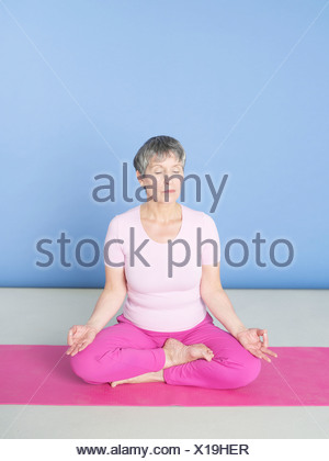 Senior woman sitting in lotus position - Stock Photo