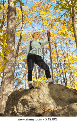 USA, New Jersey, Female hiker resting on rock in forest - Stock Photo
