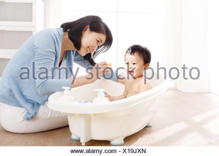 mother giving son bubble bath - Stock Photo