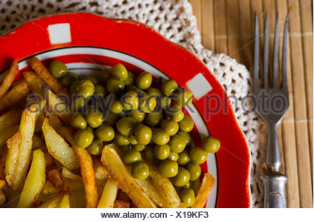 Fried potatoes with green peas - Stock Photo