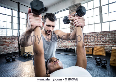 Personal trainer working with client holding dumbbell - Stock Photo