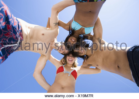 Low angle view of four young people in a huddle on the beach - Stock Photo