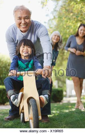 Older man pushing grandson in backyard - Stock Photo