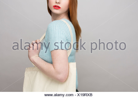 Cropped image of young woman carrying shopping bag - Stock Photo