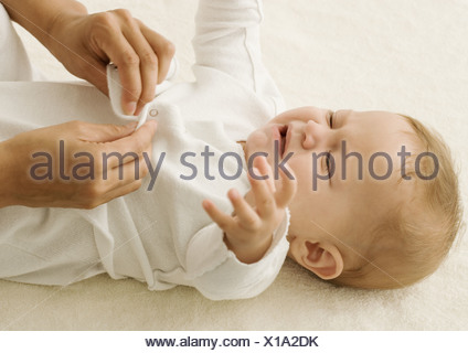 Baby being dressed, crying - Stock Photo