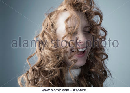 Portrait playful Caucasian woman with messy red curly hair in face - Stock Photo