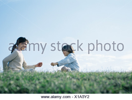 Boy and girl sitting on grass playing rock paper scissors - Stock Photo