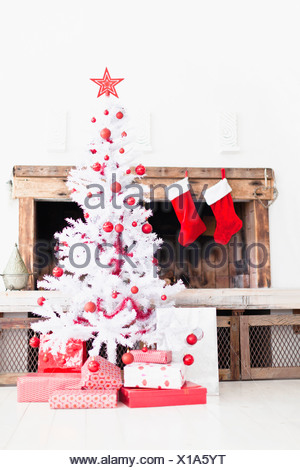 Christmas tree with gifts and stockings - Stock Photo