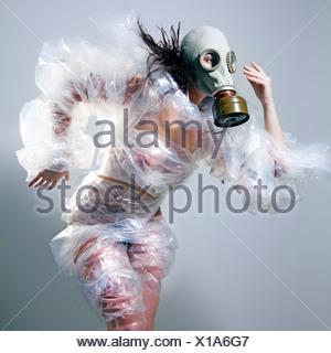 Conceptual image of a young woman wearing a gas mask covered in plastic wrapping - Stock Photo