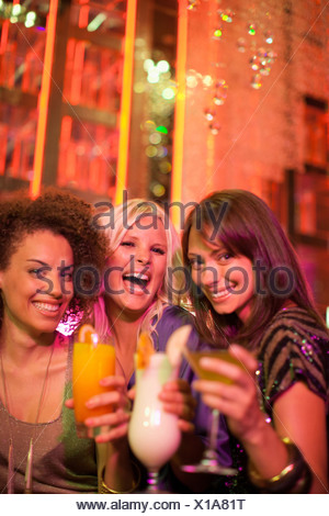 Friends drinking cocktail in nightclub - Stock Photo