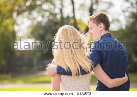 Rear view of romantic young couple strolling in park - Stock Photo