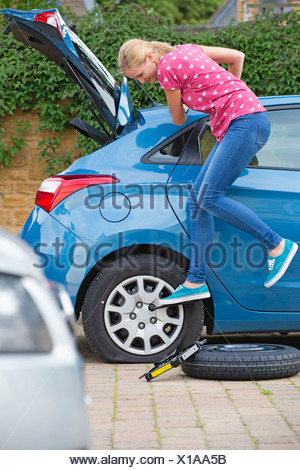 Woman Changing Flat Tyre On Car - Stock Photo