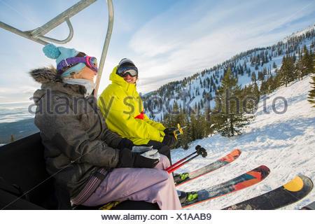 Couple in skiwear sitting on ski lift - Stock Photo