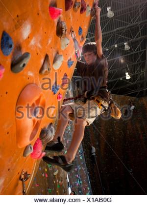 USA, Utah, Sandy, boy (12-13) on indoor climbing wall - Stock Photo