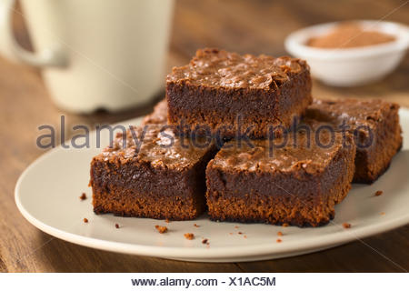 Freshly baked brownie pieces on a plate with cup in the back (Selective Focus, Focus on the left front part of the upper brownie) - Stock Photo