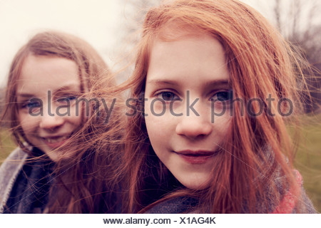 Portrait of girls wrapped in a blanket outdoors, smiling - Stock Photo