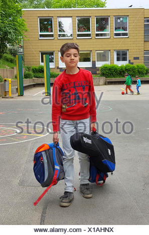 exhausted boy standing after end of school with satchel and guitar on the schoolyard - Stock Photo