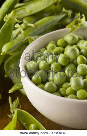 Fresh green peas with pods in the bowl on the wooden table - Stock Photo