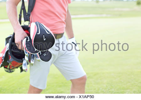 Midsection of man carrying golf club bag at course - Stock Photo
