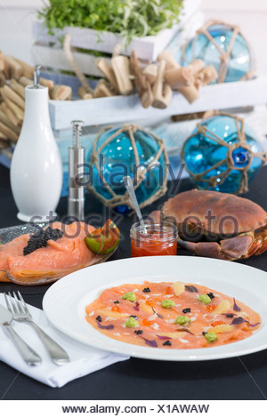 Fresh smoked salmon on a plate with fishing items. - Stock Photo