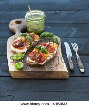 Tomato, mozzarella and basil sandwiches on dark wooden chopping board, pesto jar over black background, selective focus - Stock Photo