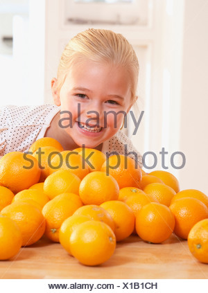 Young girl in kitchen with pile of oranges smiling - Stock Photo