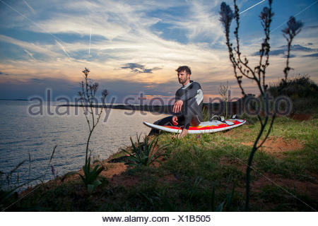 Young man sitting on surfboard - Stock Photo