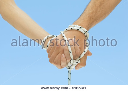 Man and woman holding hands, tied together with rope, cropped view - Stock Photo