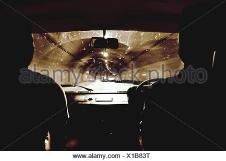 Silhouette People Driving Car In Illuminated Tunnel - Stock Photo