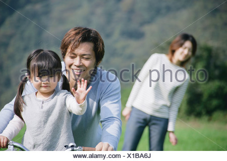 Father and daughter riding bike in meadow - Stock Photo